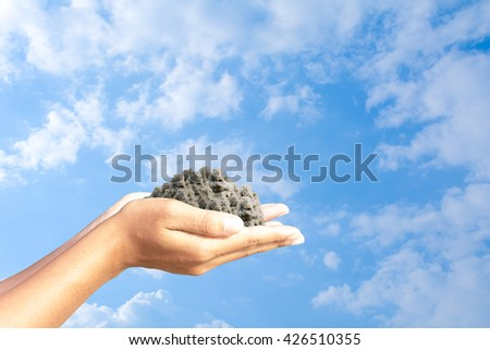 Lumps of earth in human hands Sky background - stock photo