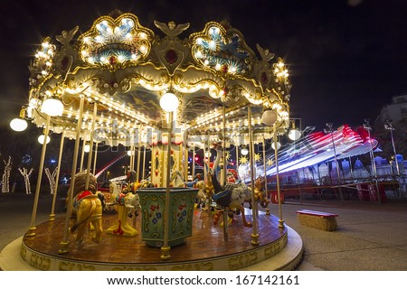 Luna park  in a public outdoor area. Amusement park at night - carousel in motion - stock photo