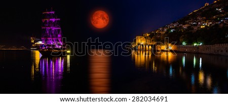 "lunar eclipse against to the dockyard of Alanya, Turkey  ""Elements of this image furnished by NASA"" - stock photo"