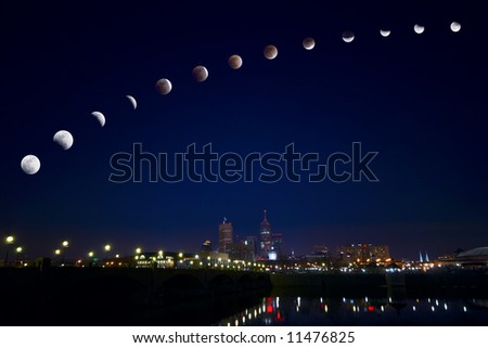 Lunar eclipse over city - stock photo