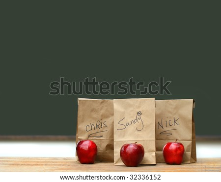 Lunch bags on desk with red apples in front of green chalkboard - stock photo