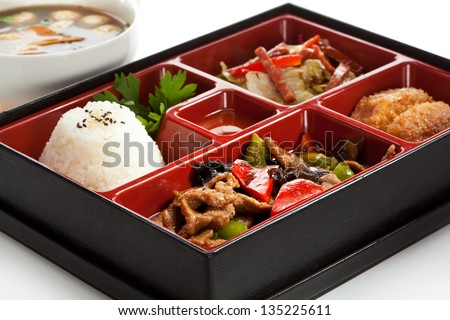 Lunch Box (Bento) - Meat with Mushrooms, Cabbage Salad, Rice and Deep Fried Banana - stock photo
