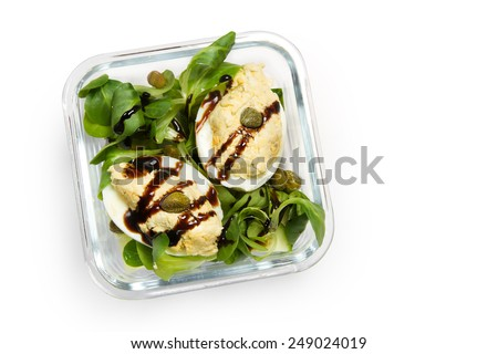 Lunch Box: eggs with cheese pate, cucumber, corn salad, capers and balsamic sauce - stock photo