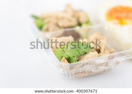 lunch box has rice, fried egg, stir meat on white background