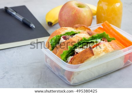 Lunch box with chicken salad sandwiches, served with carrot sticks. Fruits and juice on background, horizontal, copy space