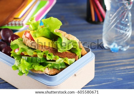 Lunch box with delicious food and stationery on blue wooden background