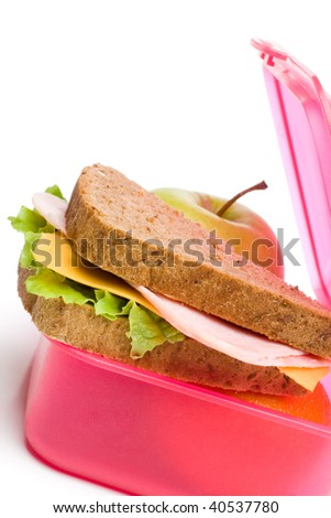 lunch box with sandwich and apple in vertical composition - stock photo