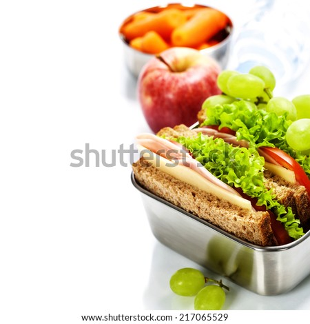Lunch box with sandwich, fruits and water on white background - stock photo