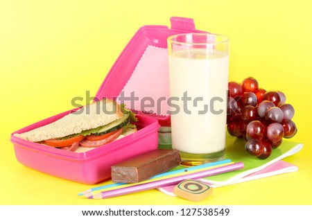Lunch box with sandwich,grape,milk and stationery on yellow background - stock photo