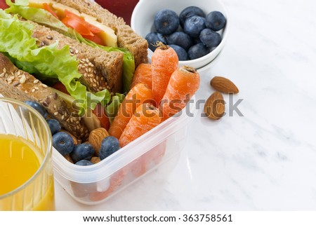 lunch box with sandwich of wholemeal bread on white background, closeup - stock photo