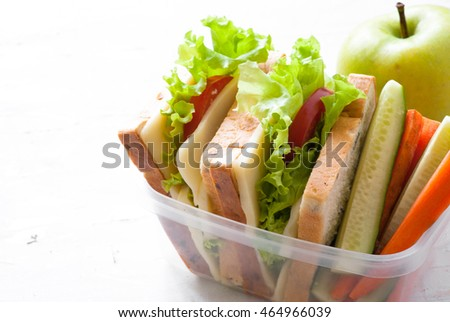 Lunch box with sandwich, vegetables,  on white. Healthy eating.