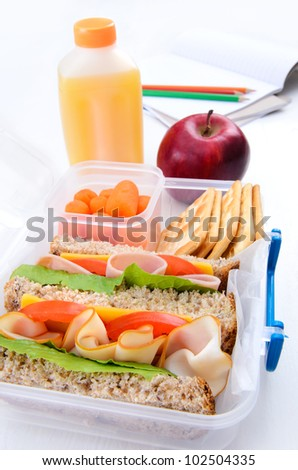 Lunch box with turkey and ham sandwich, crackers, baby carrots, apple and orange juice - stock photo