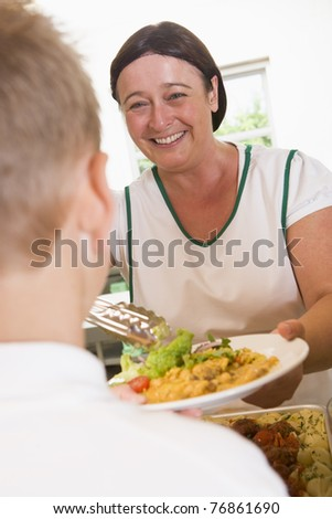 Lunch lady serving salad to student - stock photo