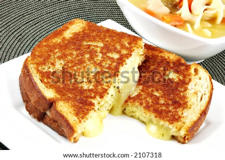 Lunch of a grilled cheese sandwich and a bowl of chicken noodle soup
