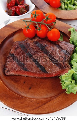 lunch of fresh rich juicy grilled beef meat steak fillet with marks on wooden plate over white table served with vegetable salad and cutlery, new york styled cuisine - stock photo