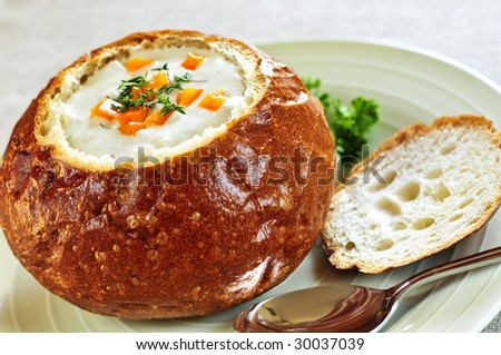 Lunch of soup served in baked round bread bowl - stock photo