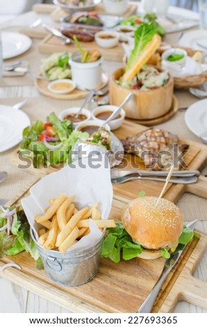 Lunch set with Hamburger with juicy beef and cheese with potato and vegetables salad - stock photo