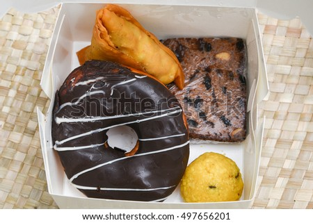 lunch/snack box with sweets/Mithai for diwali, Indian junk food like chocolate doughnut, laddu, cake, Fried Potato Samosa popular in India