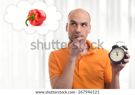 lunch time. Man holding alarm clock and dreams about food - stock photo