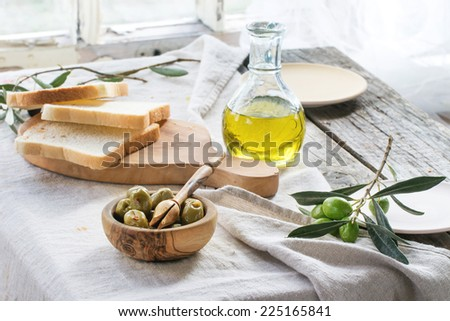 Lunch with green olives, bread and olive oil served on old wooden table near window. See series
