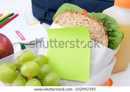 Lunchbox filled with sandwich, fruit and yogurt with post it note - stock photo