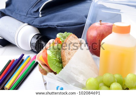 Lunchbox with ham sandwich and fruit with schoolbag and colouring pencils - stock photo