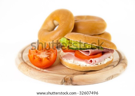 Lunchtime bagels filled with ham and cream cheese on wooden board with tomato garnish - stock photo