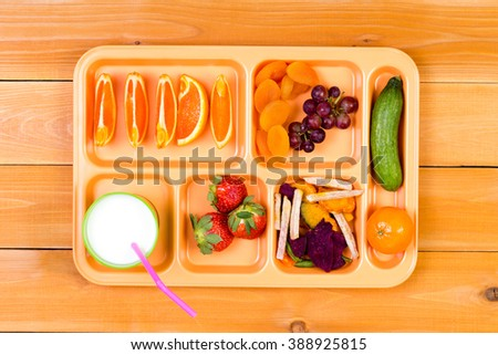 Lunchtime plastic tray filled with orange wedges, dried apricot, grapes, pickle, strawberry and other ingredients next to cup of milk over wooden table background - stock photo