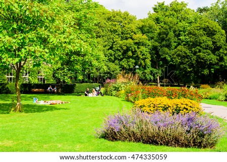 Lund, Sweden - August 24, 2016: Sunny day in the public botanical garden with people enjoying the warmth and tranquility of the flowering environment.