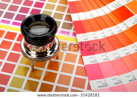 Lupe and a color guide on printed color chart (red, orange and yellow) - stock photo