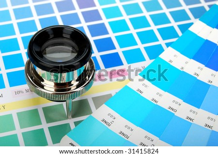 Lupe on a color chart and a color guide  (blue) - stock photo