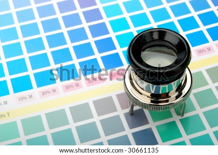 Lupe on printed color chart - stock photo