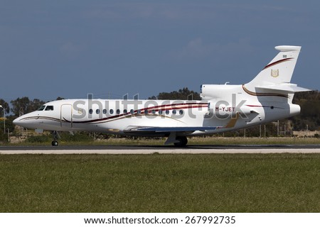 """Luqa, Malta April 9, 2015: A private Dassault Falcon 7X starting its takeoff run. Even though it is still 17 Celsius, heat haze is already quite visible. A """"cool"""" registration M-Y JET. - stock photo"""