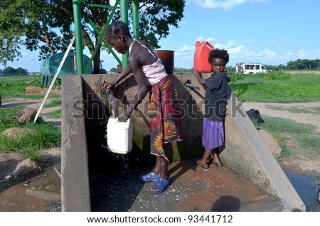 LUSAKA,ZAMBIA–DECEMBER 3:Unidentified African children fetch water many miles away from home and do not attend school to help their family,on December 3,2011  in Lusaka,Zambia - stock photo