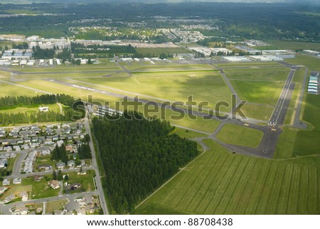 Lush green airport on partially cloudy day - stock photo