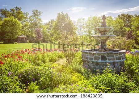 Lush green garden with stone fountain and gazebo in early morning. St. Anne's spa, Grafton, Ontario, Canada. - stock photo