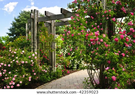 Lush green garden with stone landscaping, flowers, and arbor - stock photo