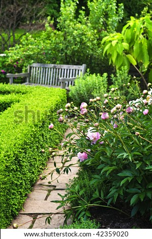 Lush green garden with stone landscaping, flowers, hedge and bench - stock photo