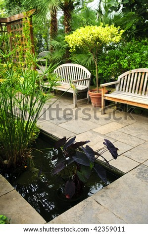 Lush green garden with stone landscaping, pond and benches - stock photo