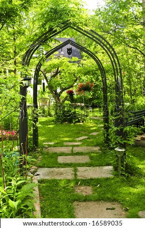 Lush green garden with wrought iron arbor stock photo