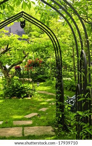 Lush green garden with wrought iron arbor - stock photo