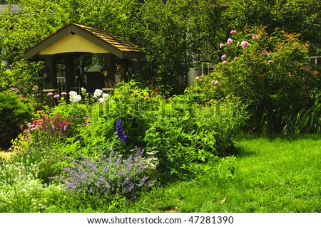 Lush green landscaped garden with flowers and gazebo - stock photo
