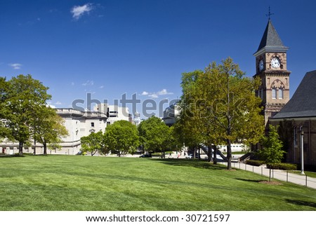 Lush green lawn and trees at the UW campus in Madison, Wisconsin, contrasts with the state capitol building in the distance. - stock photo