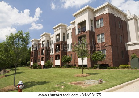 lush green lawn, tree form shrubs, and young trees beautify a brick and stucco apartment building - stock photo
