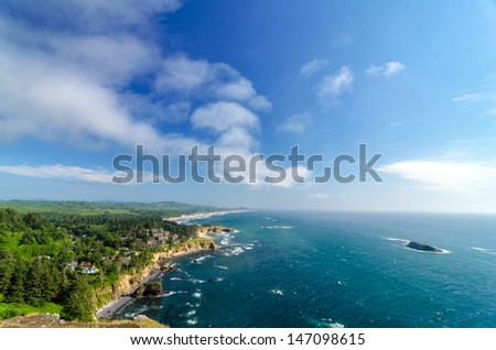 Lush green Oregon coast with blue sky and Pacific Ocean - stock photo