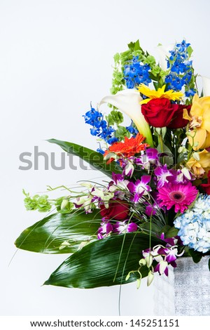 Lush holiday bouquet full of orchids, roses and lillies in silver vase - stock photo