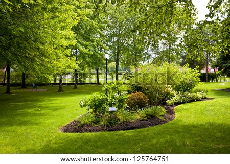 Lush landscaped grounds with garden in city park - stock photo