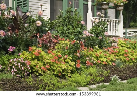 Lush ornamental garden in front of vintage farmhouse, late summer, northern Illinois - stock photo