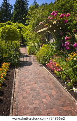Lush summer garden with paved path and blooming flowers - stock photo