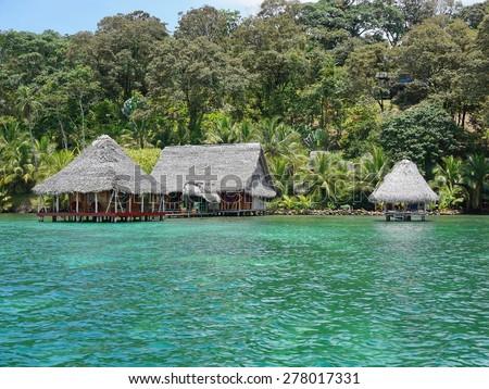 Lush tropical shore with small eco resort over the Caribbean sea in Panama, Bocas del Toro, Central America - stock photo